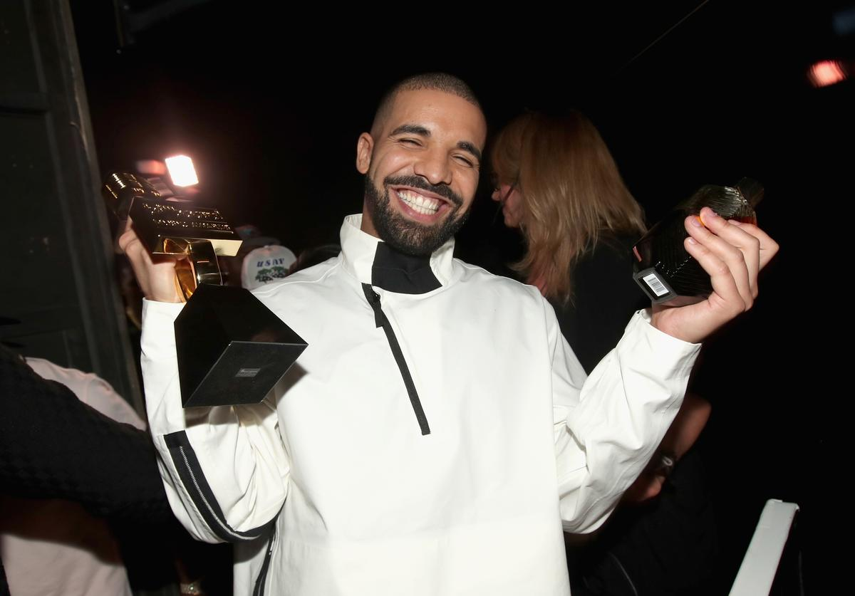 Drake smiling super big while holding up two awards