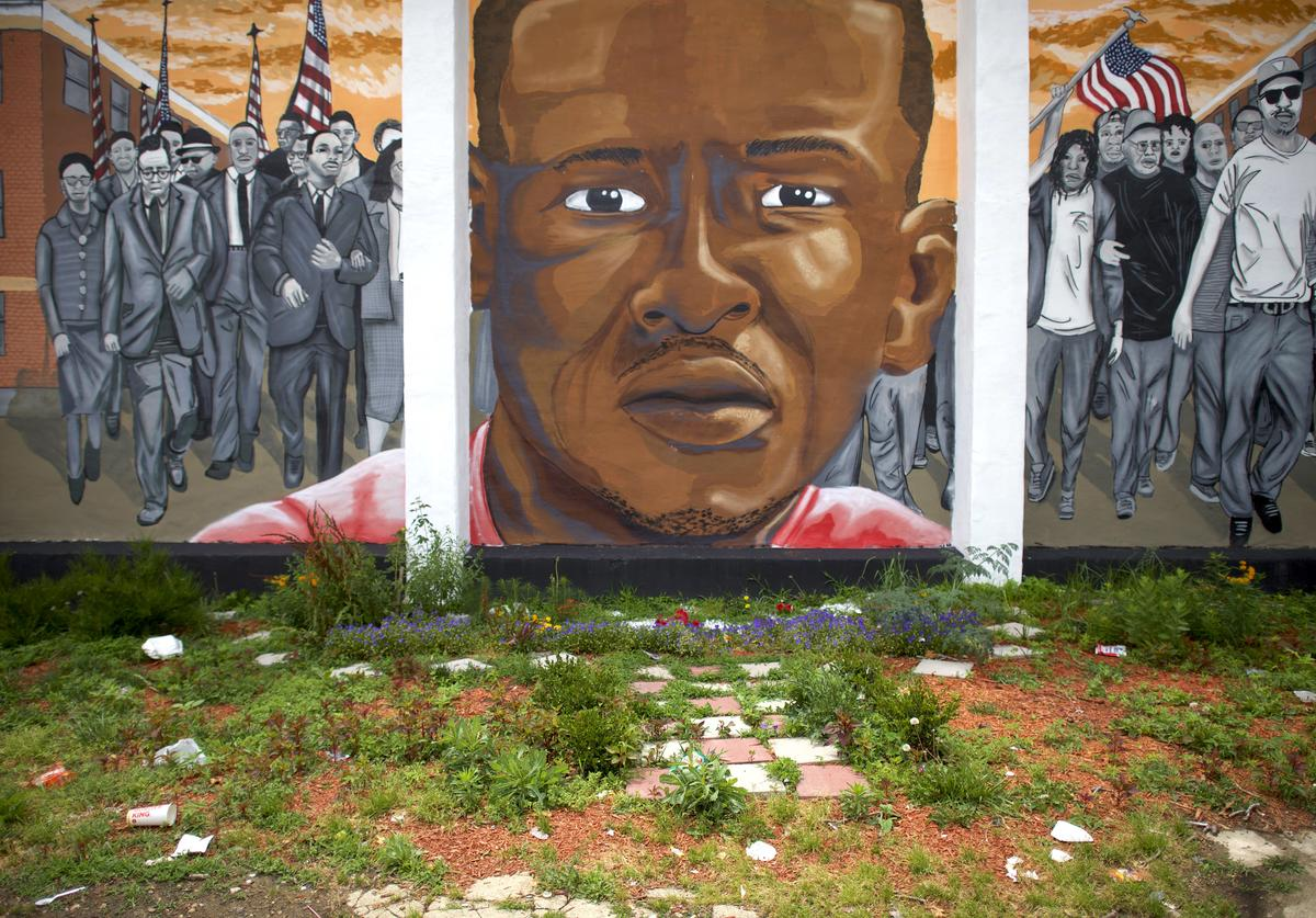 Trash collects below a mural of Freddie Gray after Baltimore police officer Caesar Goodson Jr. was found not guilty on all charges