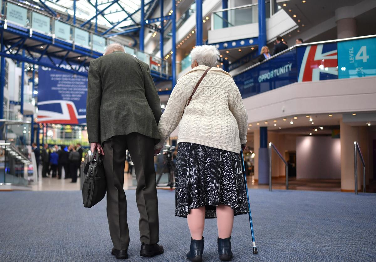 An elderly couple arrive at the Conservative Party Conference