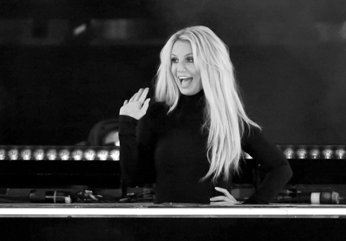 Singer Britney Spears waves as she attends the announcement of her new residency,