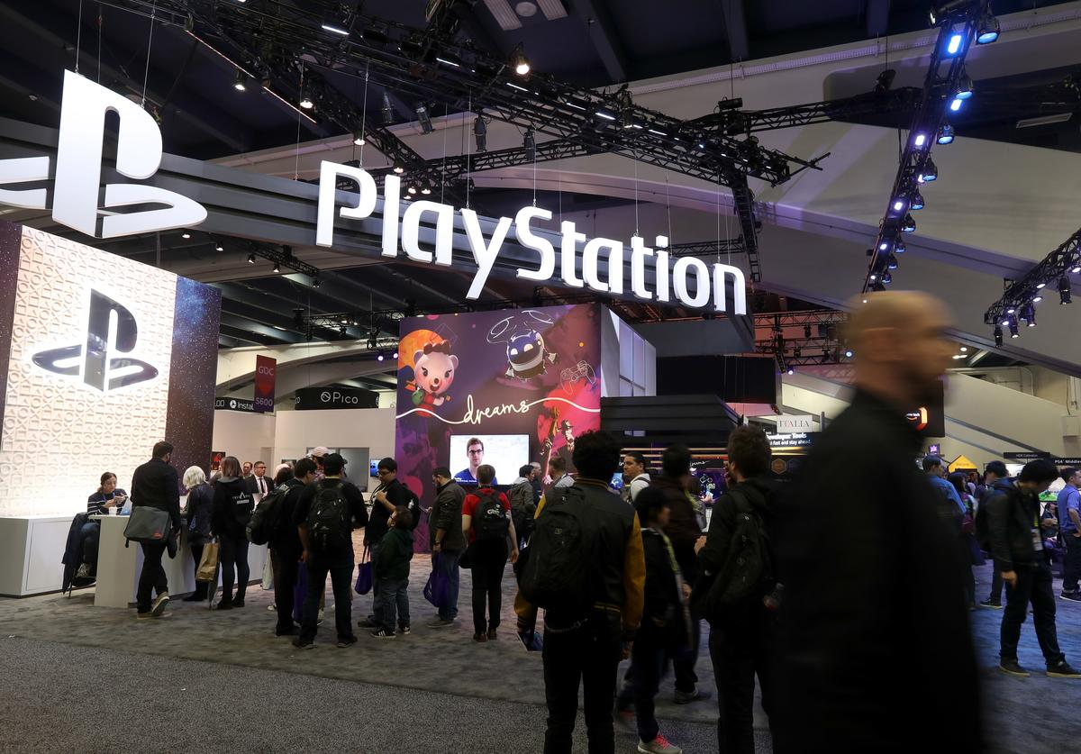 Attendees walk by the Sony PlayStation booth at the 2019 GDC Game Developers Conference on March 20,