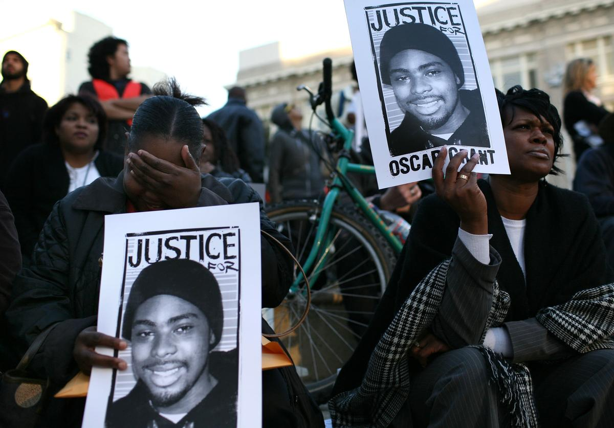Protestors carry signs with a picture of slain 22-year-old Oscar Grant III during a demonstration at Oakland City Hall