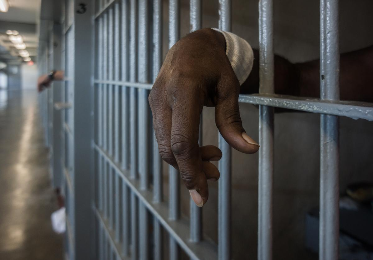 A prisoner's hands inside a punishment cell wing at Angola prison.