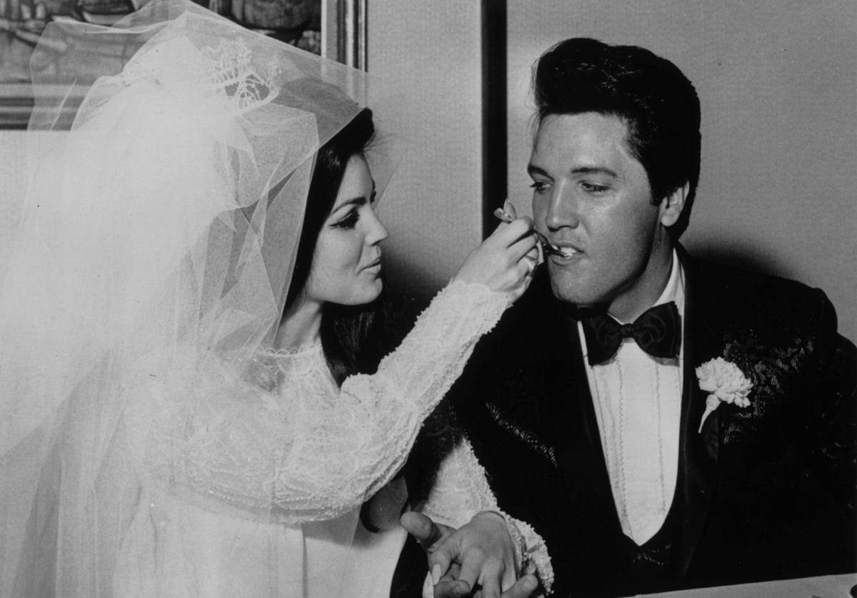 Elvis Presley (1935 - 1977) being fed a mouthful of wedding cake by his bride Priscilla Beaulieu