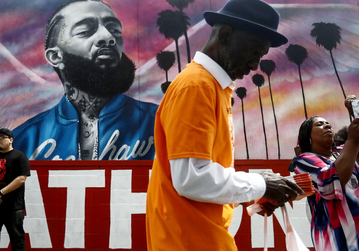 People gather and take photos in front of a mural to slain rapper Nipsey Hussle as they await the funeral procession