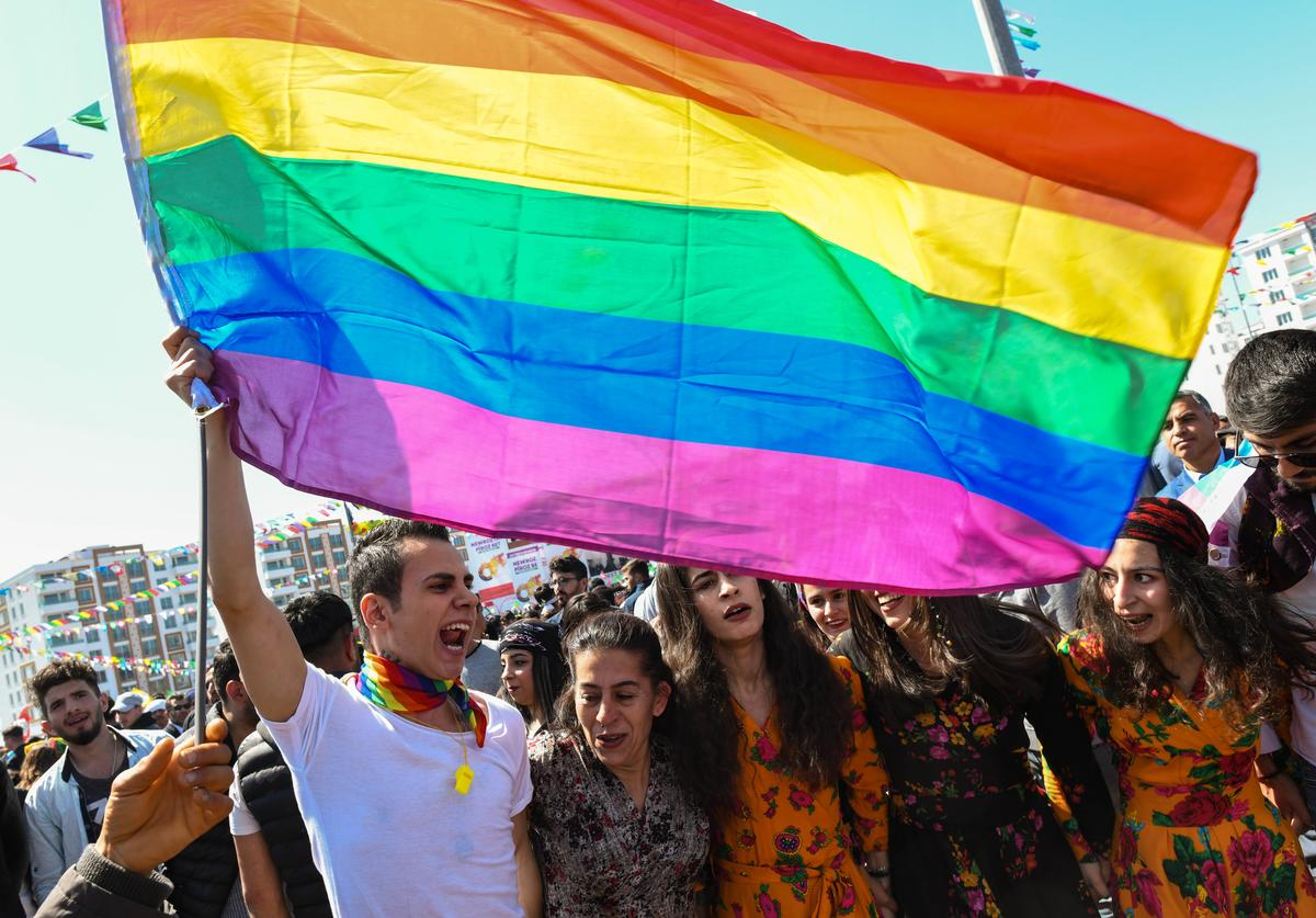 A man waves A rainbow flag (often used by the LGBT community)