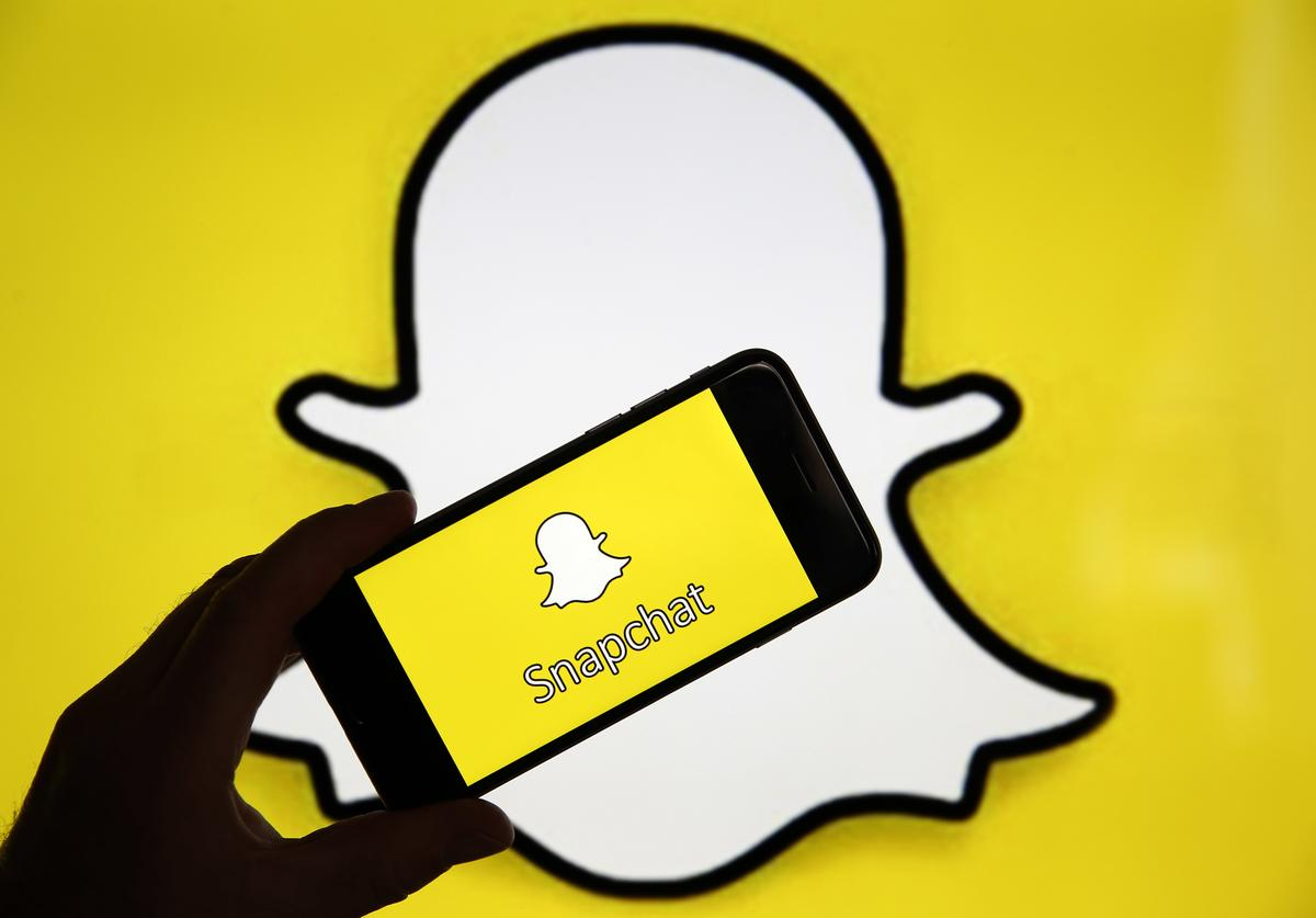 In this photo iIllustration, the Snapchat social media logo is displayed on the screen of an iPhone
