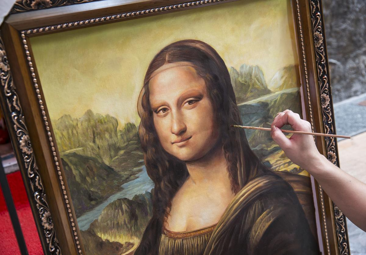 A artist works on a replica of the famous Mona Lisa outside a gallery