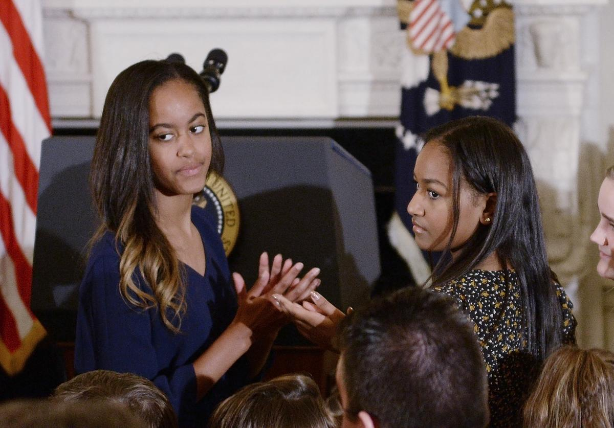 Malia Obama (L) and Sasha Obama look on durinng a ceremony presenting the Medal of Freedom to Vice-President Joe Biden at the State Dining room of the White House on January 12, 2017 in Washington, DC