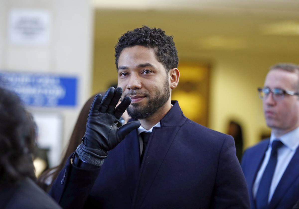 Actor Jussie Smollett waves as he follows his attorney to the microphones after his court appearance at Leighton Courthouse