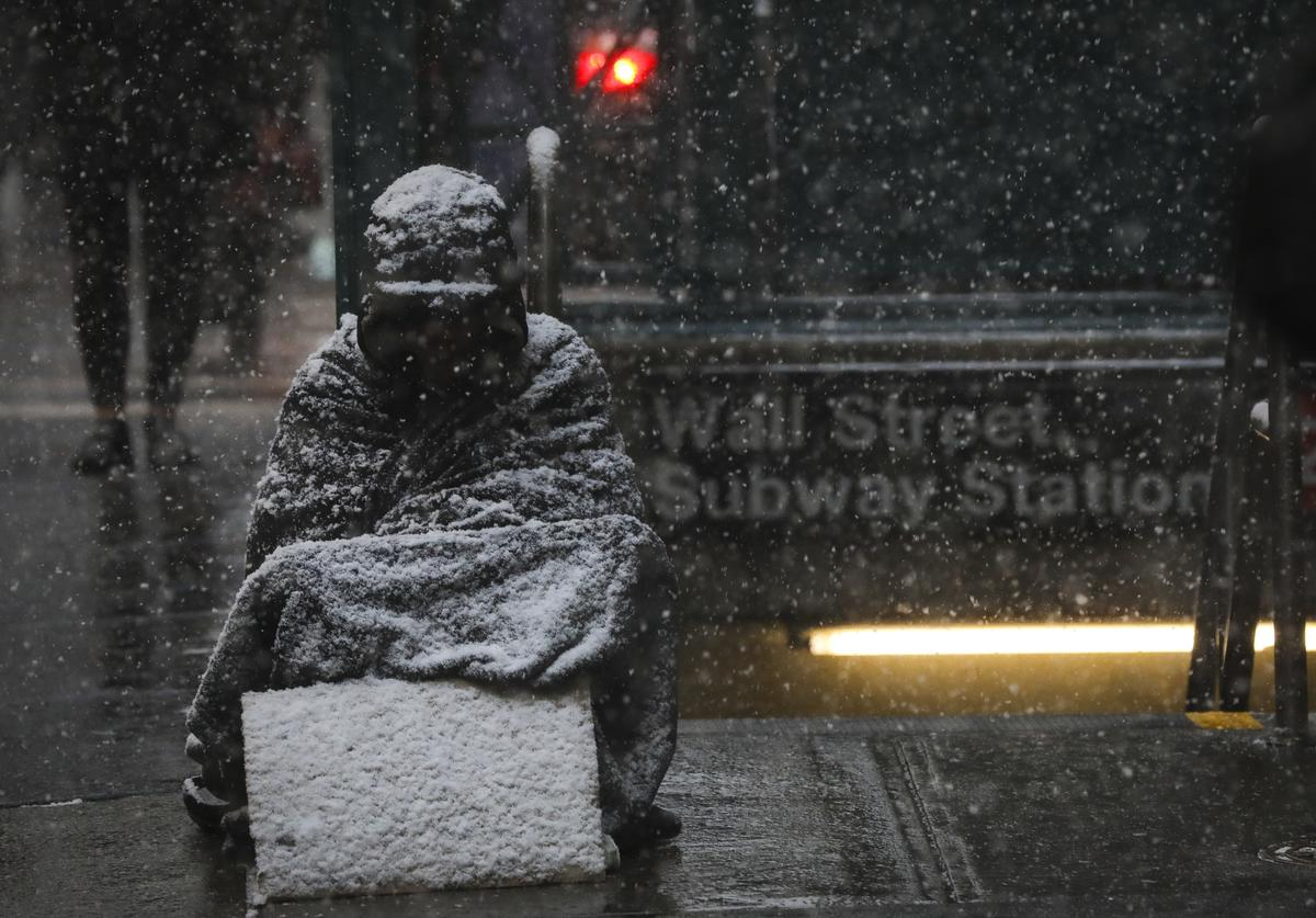A homeless man sits in the falling snow in the Financial District, January 30, 2019