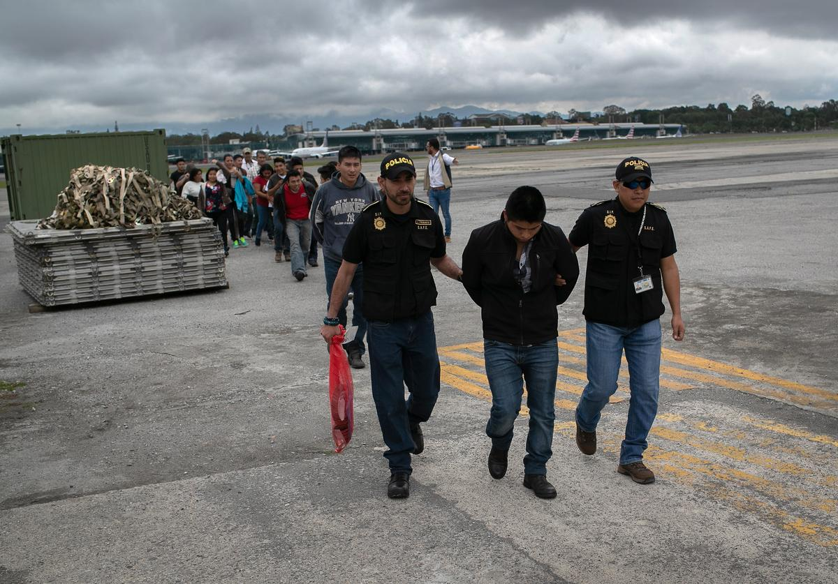 Guatemalan police escort an accused criminal on the airport tarmac