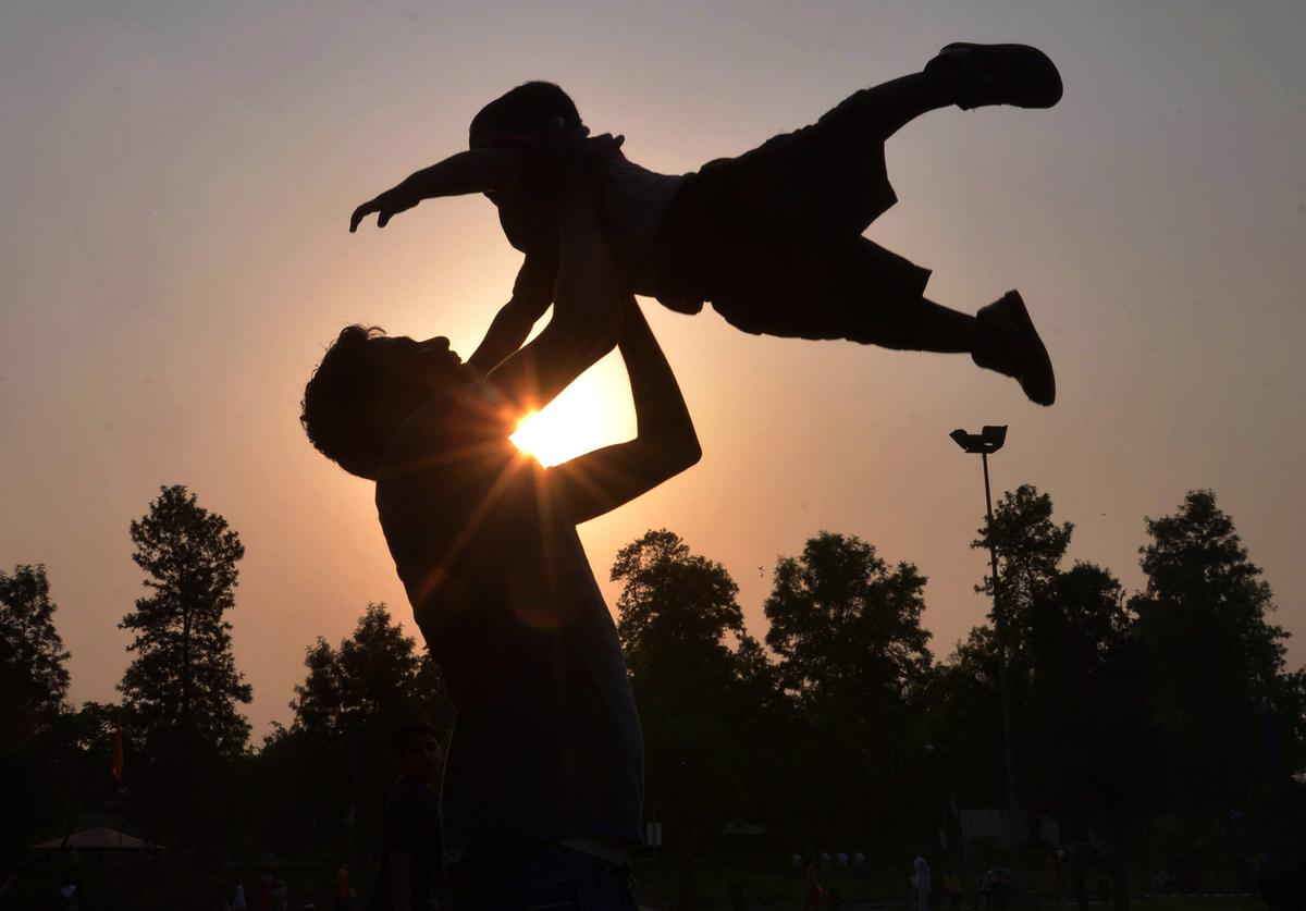 Indian father Shailesh throws up his son, Harish, at a park in Amritsar on June 19, 2016, on Father's Day, a day observed in many countries to celebrate fathers and fatherhood