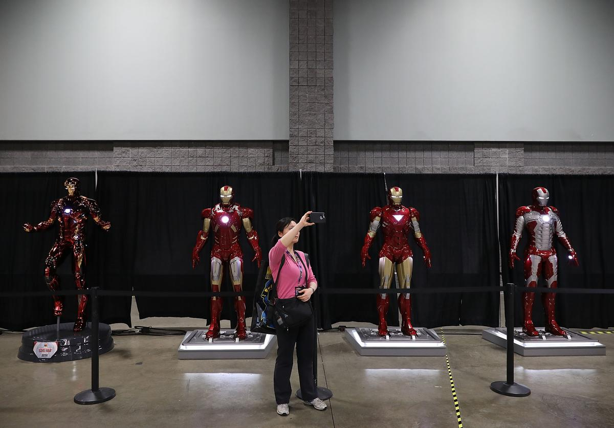 A woman stops to take a selfie with lifesize Ironman models in the Stan Lee Museum
