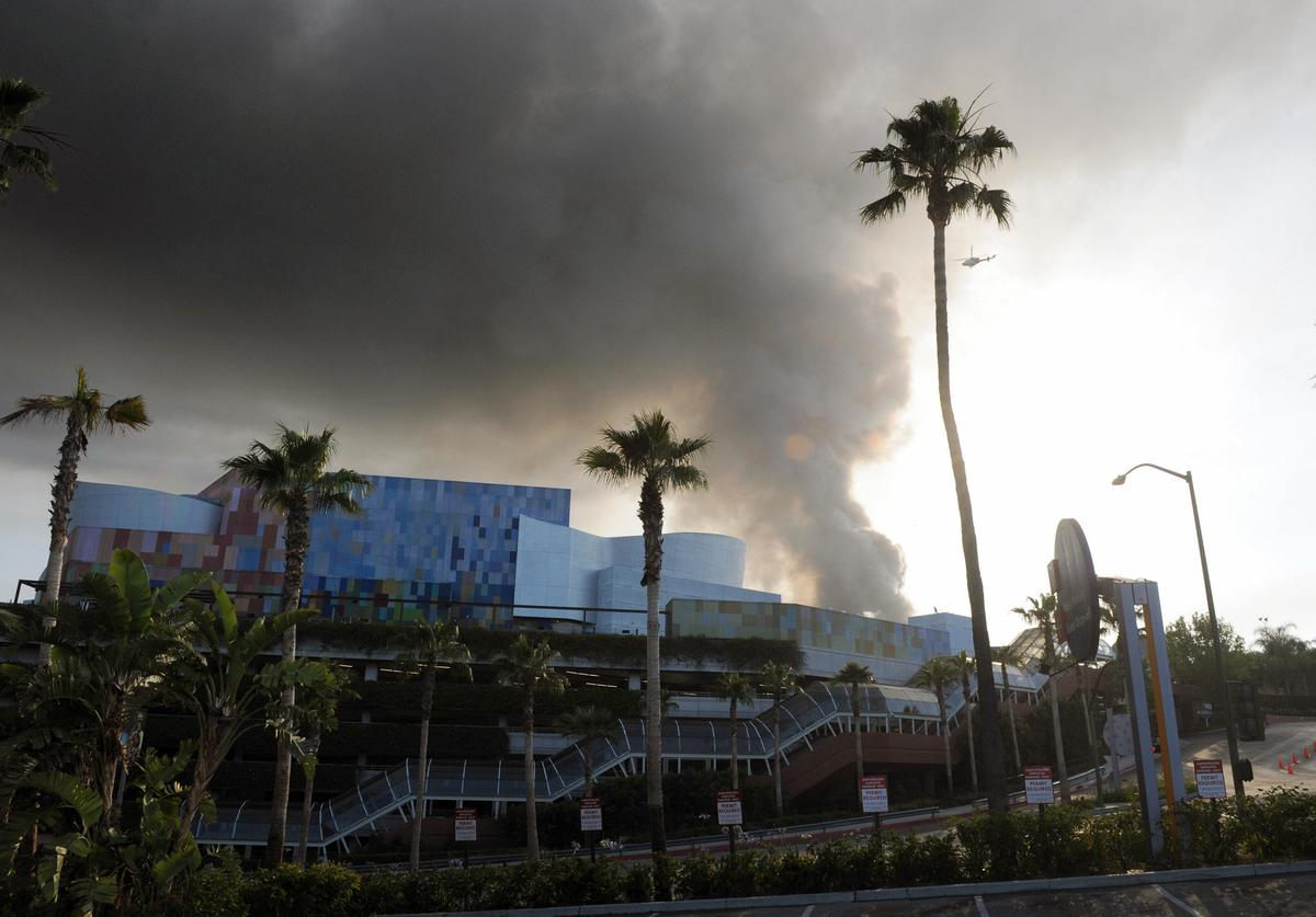 A helicopter flies over burning structures at Universal Studios, in Universal City, California, on June 01, 2008
