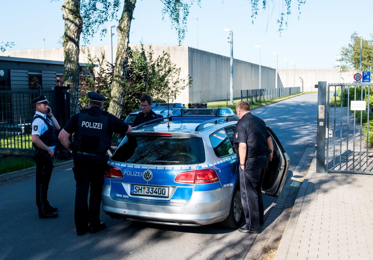 Police officers work at the scene where a man has taken two people hostage at a prision in Luebeck
