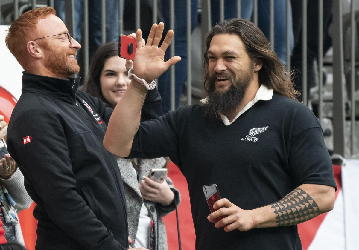 Jason Momoa waves to fans while taking in the rugby sevens action on Day 2
