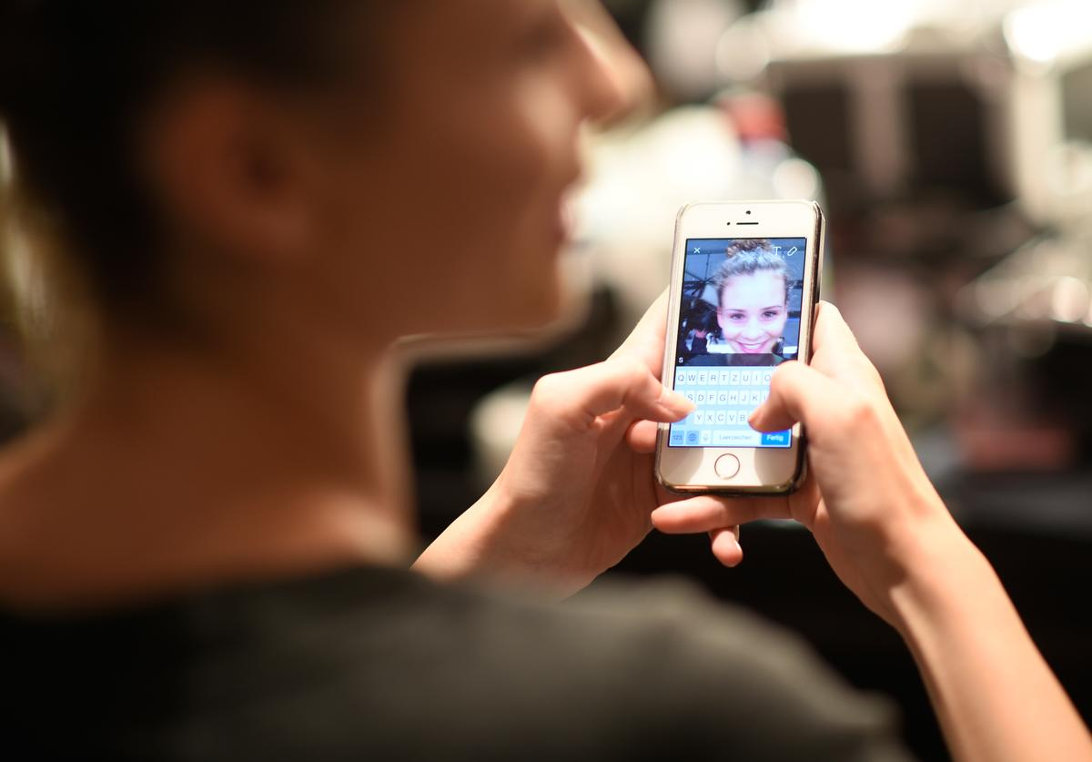 A model texting on her mobile is seen backstage ahead of the 'Designer for Tomorrow'