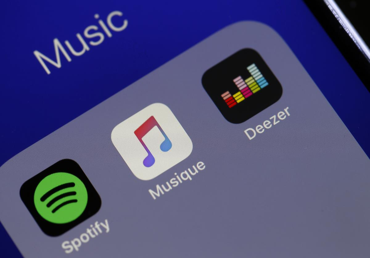 In this photo illustration, the logos of the applications, Spotify, Apple Music and Deezer are displayed on the screen of an iPhone on April 08, 2019 in Paris, France. The number of paying subscribers to the music streaming service of Apple Music has for the first time exceeded that of Spotify customers in the US. The two platforms now have 28 and 26 million paying users, respectively, sources told the Wall Street Journal.