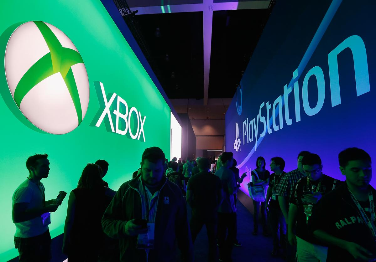 : Game enthusiasts and industry personnel walk between the Microsoft XBox and the Sony PlayStation exhibits at the Annual Gaming Industry Conference E3 at the Los Angeles Convention Center on June 16, 2015 in Los Angeles, California.