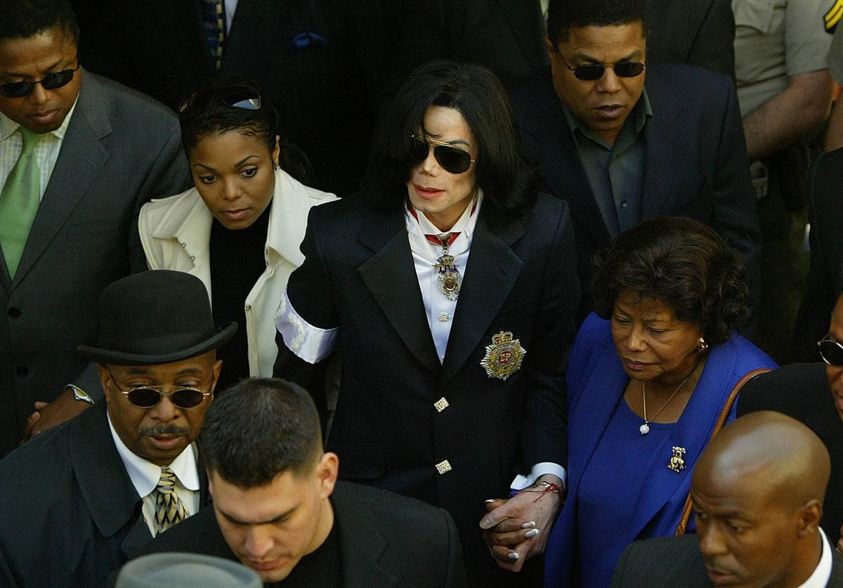 Pop star Michael Jackson holds his mother's hand as he walks with sister Janet (L) at his side as they leave his arraignment for child molestation charges January 16, 2004 at the courthouse in Santa Maria, California.