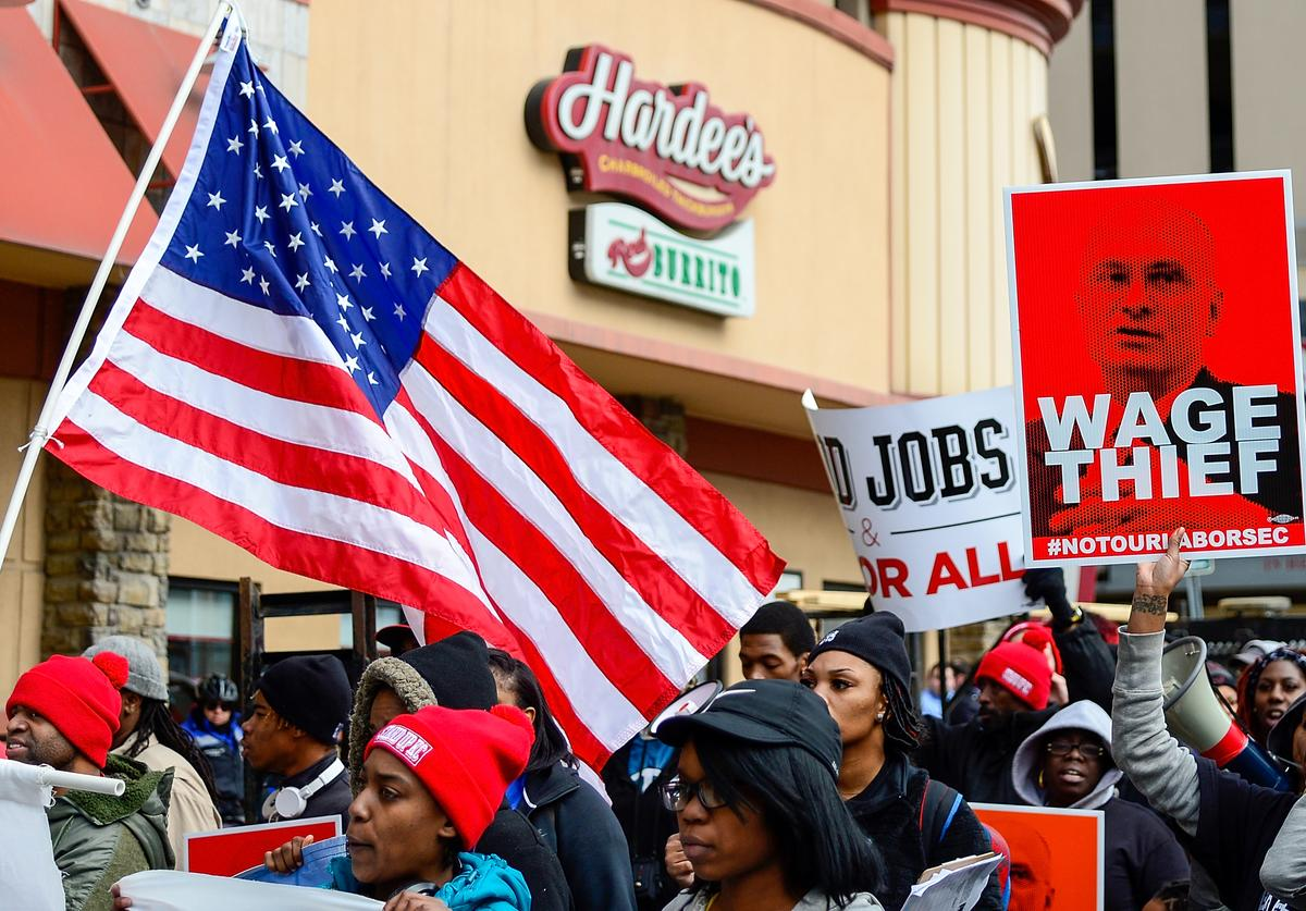 Protesters rally against Labor nominee Andrew Puzder outside of a Hardee's restaurant