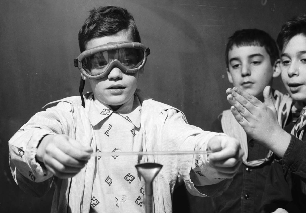A schoolboy holds a pane of glass above a bunsen burner as an experiment in glassbending, during a chemistry lesson at the Hunter College Elementary School