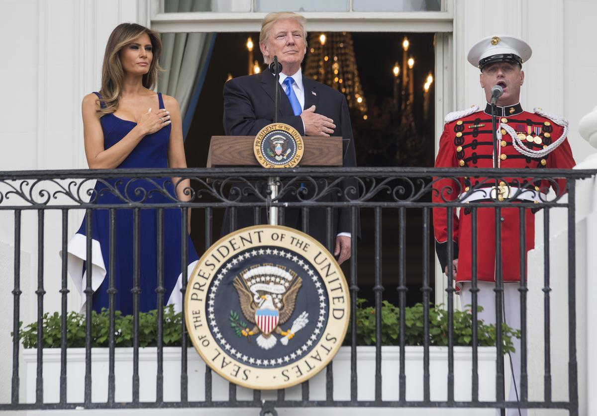 U.S. President Donald Trump and first lady Melania Trump observe the playing of the national anthem from the Truman Balcony on July 4, 2017 in Washington, DC. The president was hosting a picnic for military families for the July 4 holiday.