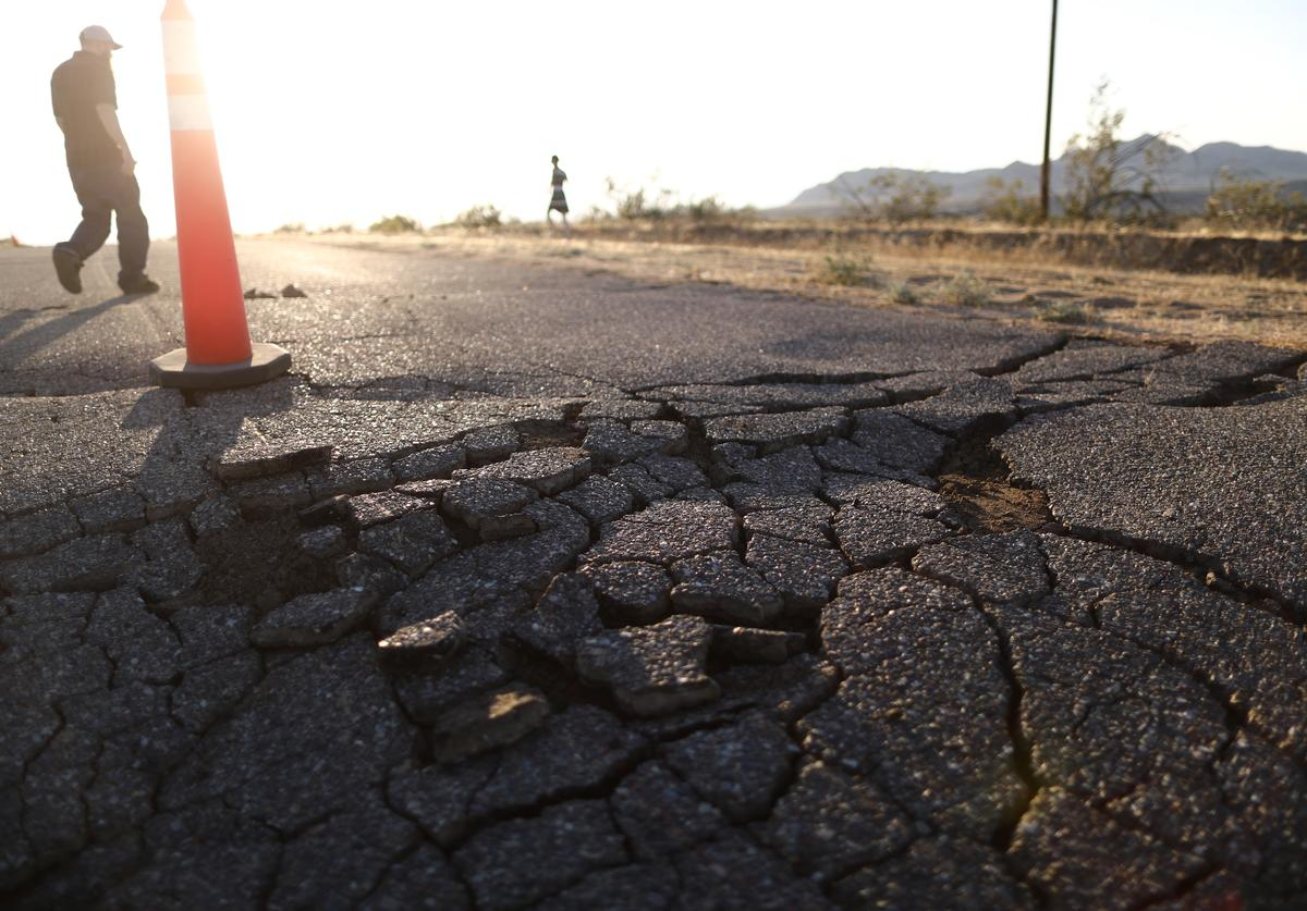 People walk near cracks in the road after a 6.4 magnitude earthquake struck the area on July 4, 2019