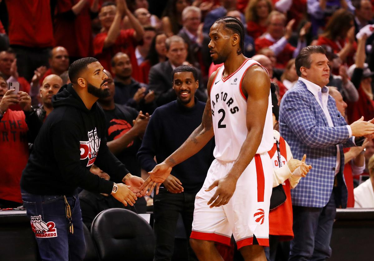 Kawhi Leonard #2 of the Toronto Raptors high fives rapper Drake during game four of the NBA Eastern Conference Finals between the Milwaukee Bucks and the Toronto Raptors at Scotiabank Arena on May 21, 2019 in Toronto, Canada.