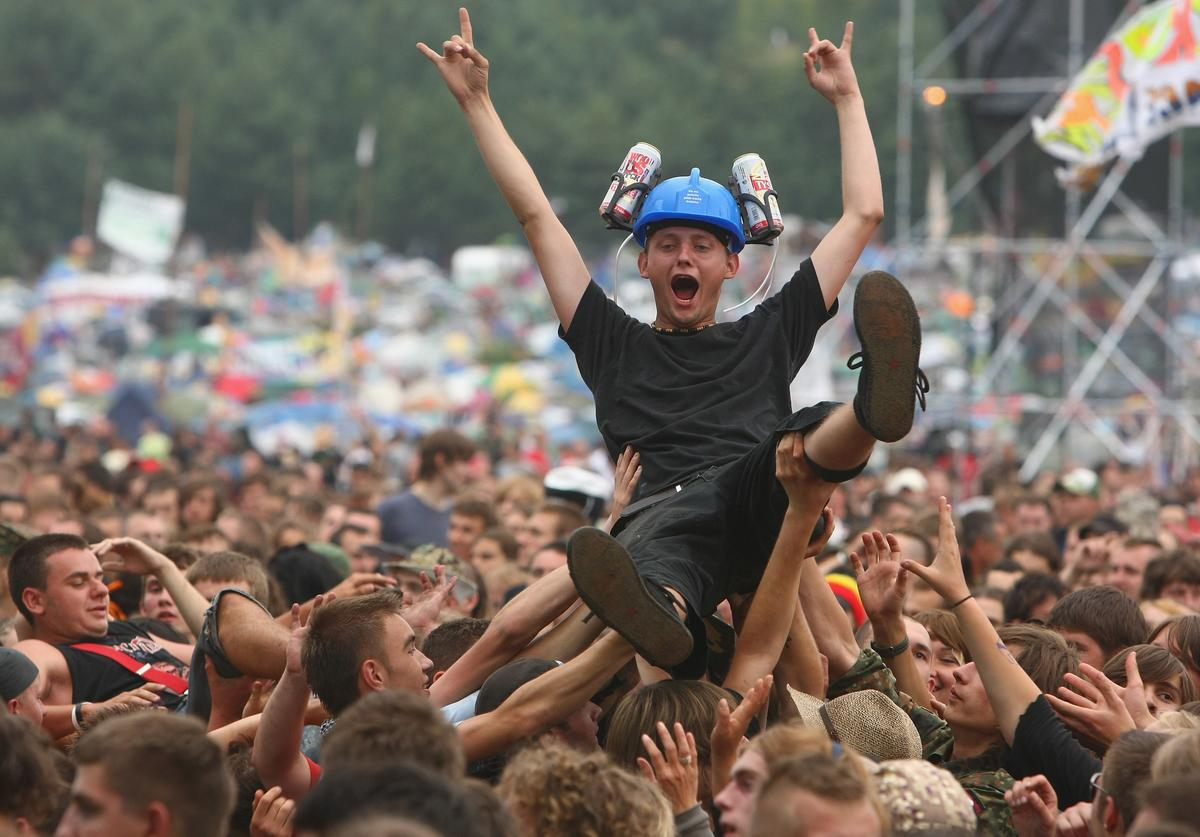 A young man with beer cans attached to a safety helemt on his head is held aloft by dancing music fans at the International Woodstock Festival on August 2, 2008 in Kostrzyn, Poland. Hundreds of thousand of fans attend the annual festival to hear bands play a wide variety of music on an open field near Kostrzyn close to the German and Polish border.