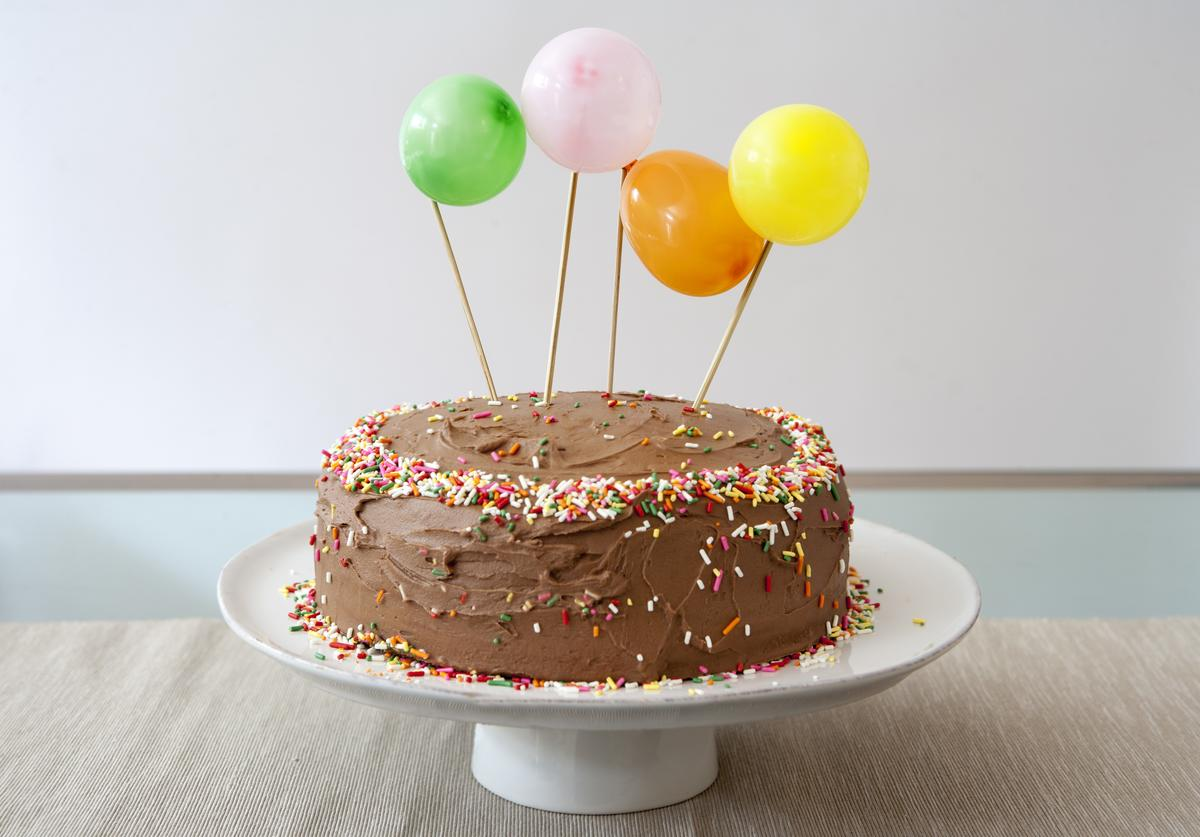 Birthday Cake with Chocolate Icing Decorated with Balloons and Sprinkles.