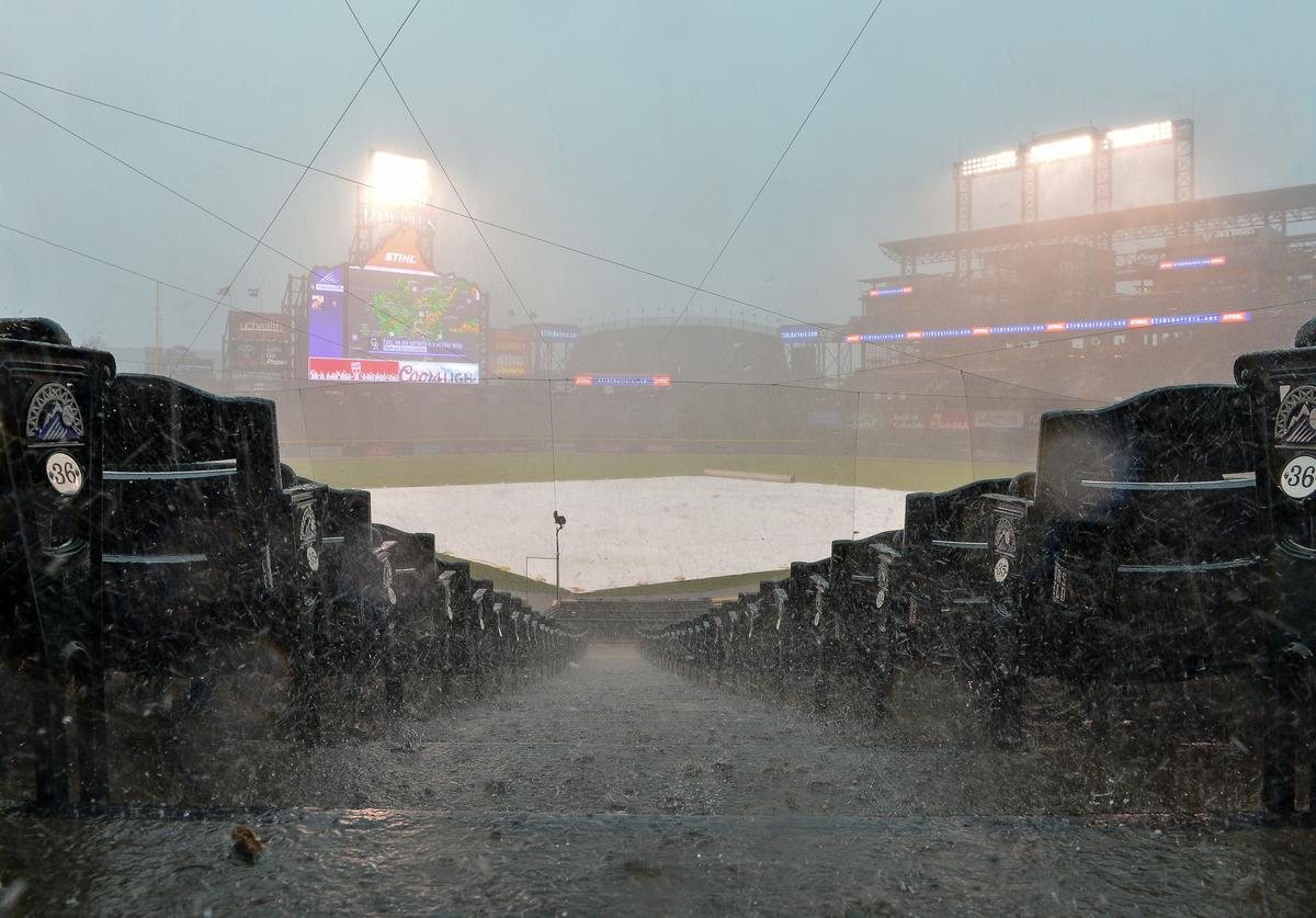 Rain and hail falls on the field during a weather delay before a scheduled game between the Colorado Rockies and the Miami Marlins at Coors Field on June 24, 2018 in Denver, Colorado
