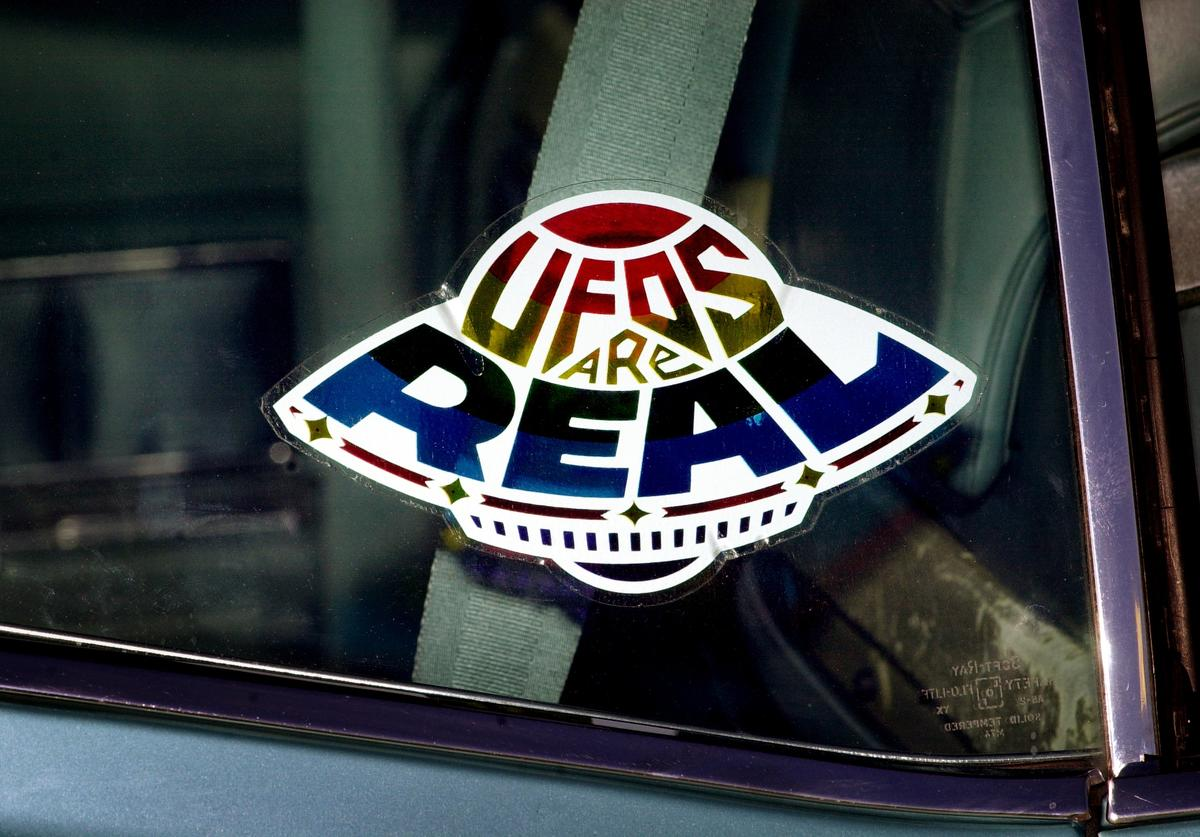 """A sticker declares the existence of flying saucers from the window of a car parked on property near Jamul, CA, October 15, 2000, purchased by the Unarius Academy of Science to serve as a future landing site for """"space brothers"""" from other planets. According to the academy, a spaceship carrying 1,000 alien scientists from the planet Myton will arrive on Earth in the year 2001, landing on a raised landform that was once part of an Atlantean continent in the Caribbean Sea. If humans are spritually ready, a total of 33 flying saucers from different planets will land in a towering stack near Jamul, CA to create an international university and introduce new technologies to save planet Earth from self-destruction"""