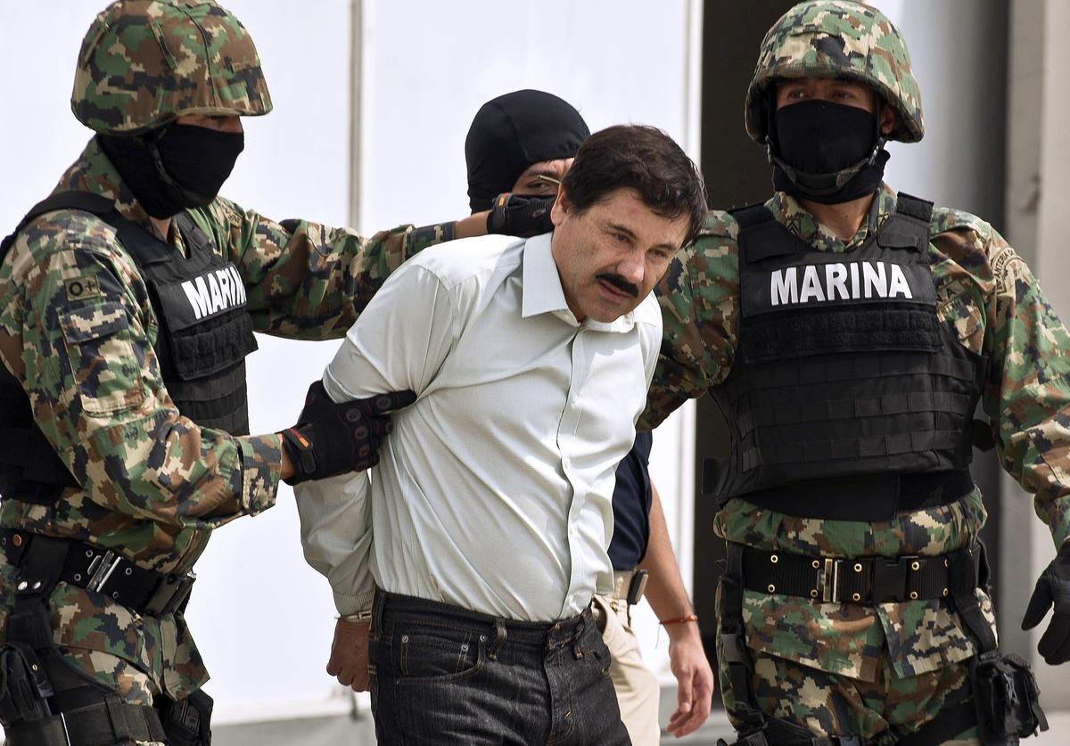 """Joaquin Guzman Loera aka """"el Chapo Guzman"""" (C), is escorted by marines as he is presented to the press on February 22, 2014 in Mexico City"""