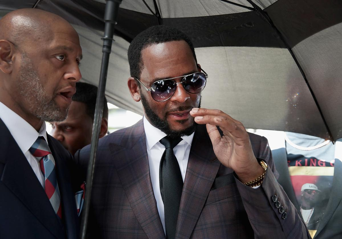 R&B singer R. Kelly (R) leaves the Leighton Criminal Courts Building following a hearing on June 26, 2019 in Chicago, Illinois. Prosecutors turned over to Kelly's defense team a DVD that alleges to show Kelly having sex with an underage girl in the 1990s. Kelly has been charged with multiple sex crimes involving four women, three of whom were underage at the time of the alleged encounters.