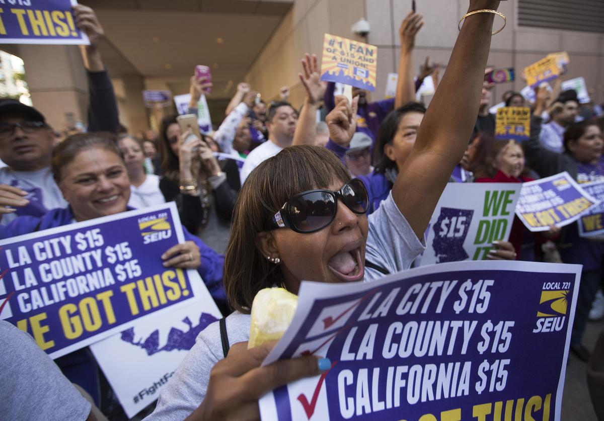 Service Employees International Union members celebrate after California Governor Jerry Brown signed landmark legislation SB 3 into law on April 4, 2016 in Los Angeles, California.