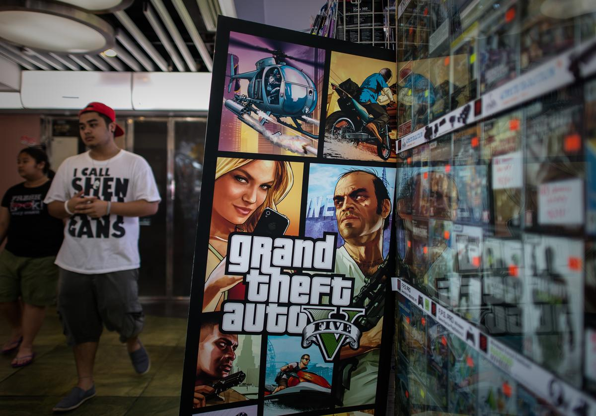 "A man walks past a billboard of the ""Grand Theft Auto V"" video game in Hong Kong on September 17, 2013."