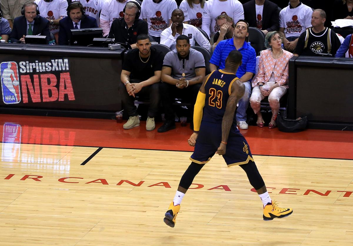 LeBron James #23 of the Cleveland Cavaliers reacts in front of rapper Drake in the fourth quarter against the Toronto Raptors in game four of the Eastern Conference Finals during the 2016 NBA Playoffs at the Air Canada Centre on May 23, 2016 in Toronto, Ontario, Canada