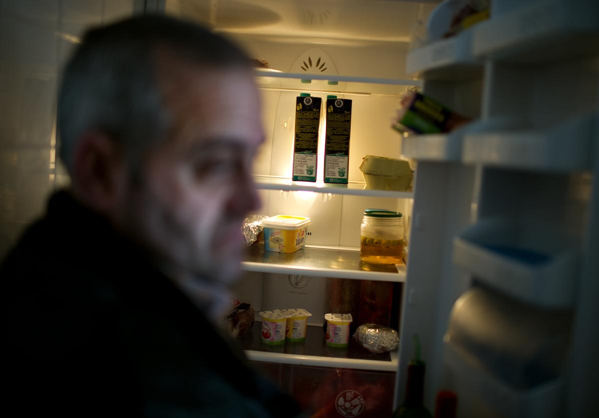 Fifty-year old unemployed former door factory worker Luis Gonzales, who has been without welfare payment now for two months being unable to pay his 160 Euro (211 US Dollars) a month morgage, his electicity and heating bills, shows the food that is left in his refrigerator after receiving the monthly Red Cross food hand out for him and his two duaghters at his home on December 21, 2012 in Villacanas, Spain. During the boom years, where in its peak Spain built some 800,000 houses a year accompanied by the manufacturing of millions of wooden doors, the people of Villacanas were part of Spain's middle class enjoying high wages and permanent jobs. During these construction boom years the majority of the doors used within these new developments were made in this small industrial town. Approximately seven million doors a year were once assembled here and the factories employed a workforce of almost 5700 people. The town is now left almost desolate with the Villacanas industrial park empty and redundant. With Spain in the grip of recession and the housing bubble burst, Villacanas is typical of many former buoyant industrial Spanish towns now struggling with huge unemployment problems.