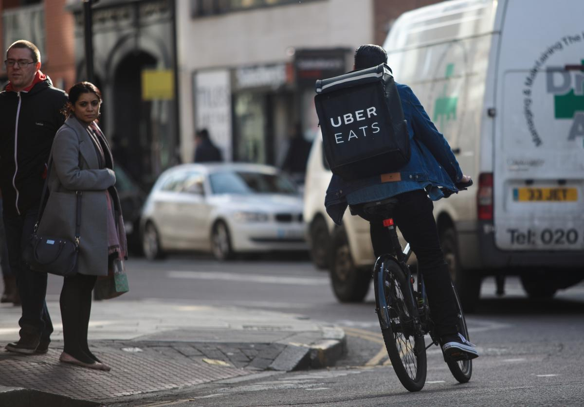An Uber Eats rider cycles through central London on February 16, 2018 in London, England