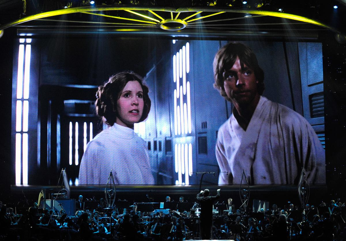 "Actress Carrie Fisher's Princess Leia Organa character and actor Mark Hamill's Luke Skywalker character from ""Star Wars Episode IV: A New Hope"" are shown on screen while musicians perform during ""Star Wars: In Concert"" at the Orleans Arena May 29, 2010 in Las Vegas, Nevada. The traveling production features a full symphony orchestra and choir playing music from all six of John Williams' Star Wars scores synchronized with footage from the films displayed on a three-story-tall, HD LED screen"