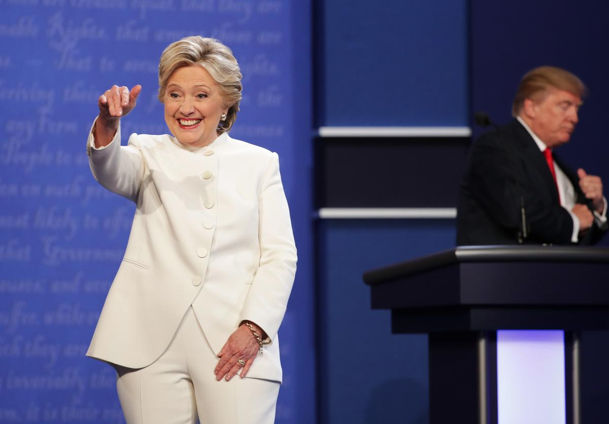 Democratic presidential nominee former Secretary of State Hillary Clinton gestures to the crowd as she walks off stage as Republican presidential nominee Donald Trump smiles after the third U.S. presidential debate at the Thomas & Mack Center on October 19, 2016 in Las Vegas, Nevada. Tonight is the final debate ahead of Election Day on November 8.