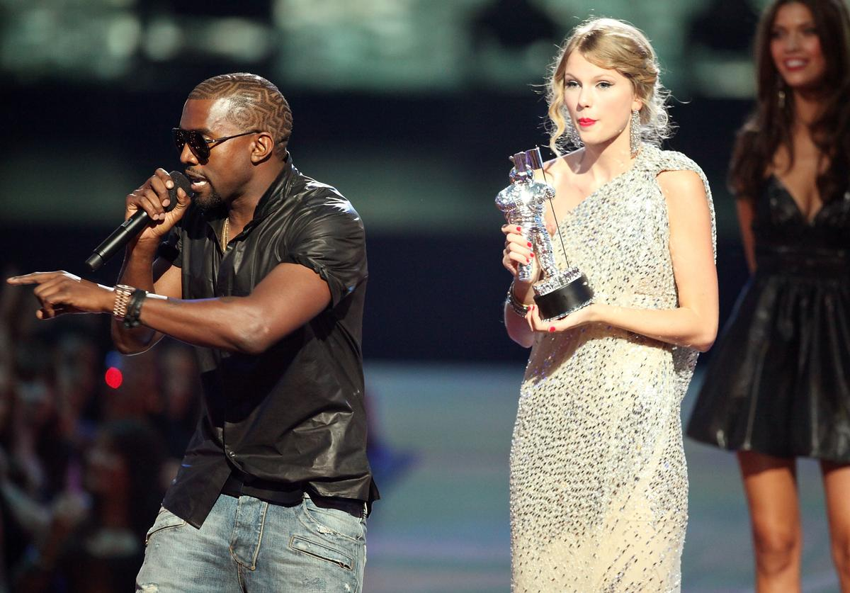 """Kanye West (L) jumps onstage after Taylor Swift (C) won the """"Best Female Video"""" award during the 2009 MTV Video Music Awards at Radio City Music Hall on September 13, 2009 in New York City. ("""