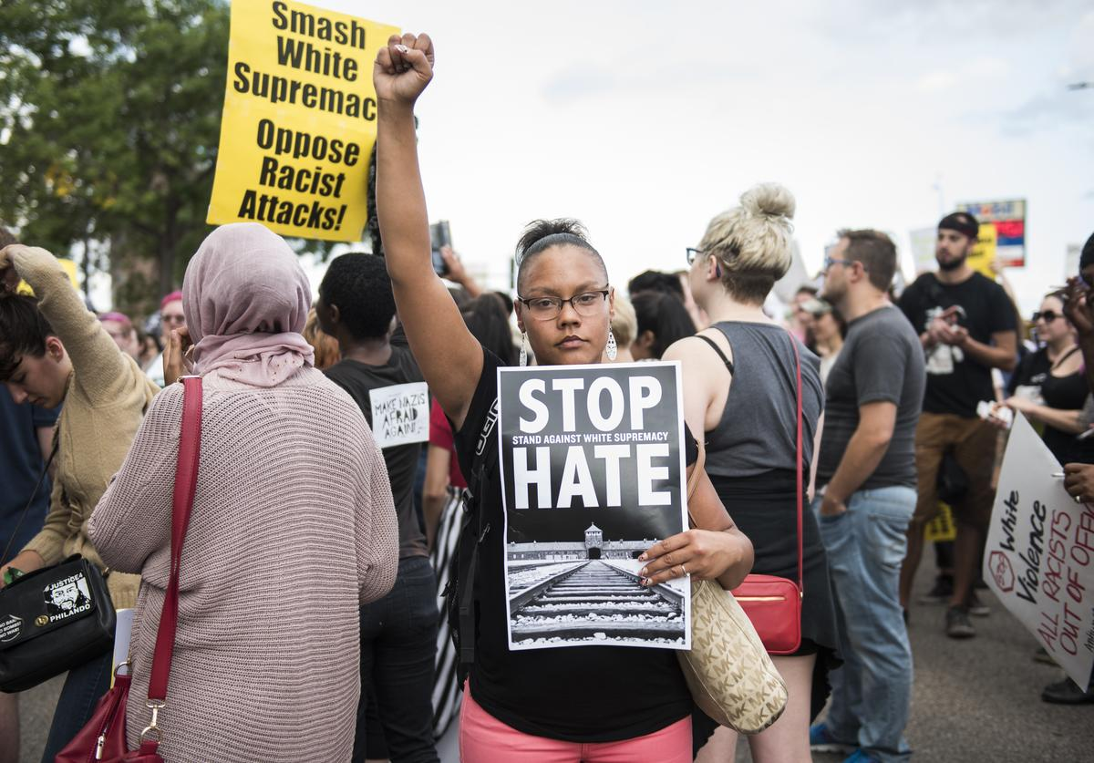 A woman raises her fist at the front of a march down Washington Avenue to protest racism and the violence over the weekend in Charlottesville, Virginia on August 14, 2017 in Minneapolis, Minnesota