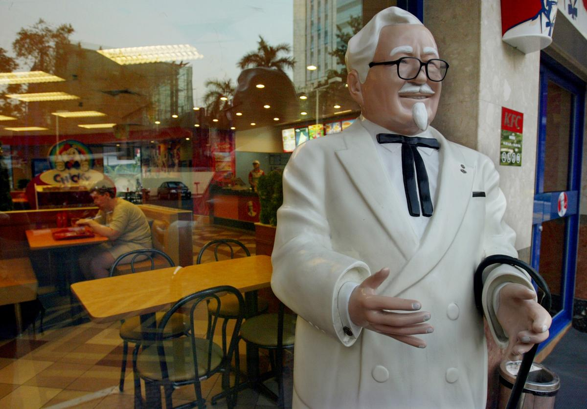 A statue of Colonel Harland Sanders, founder of Kentucky Fried Chicken (KFC) stands on the street one of the fast food restaurants in Bangkok, Thailand January 27, 2004