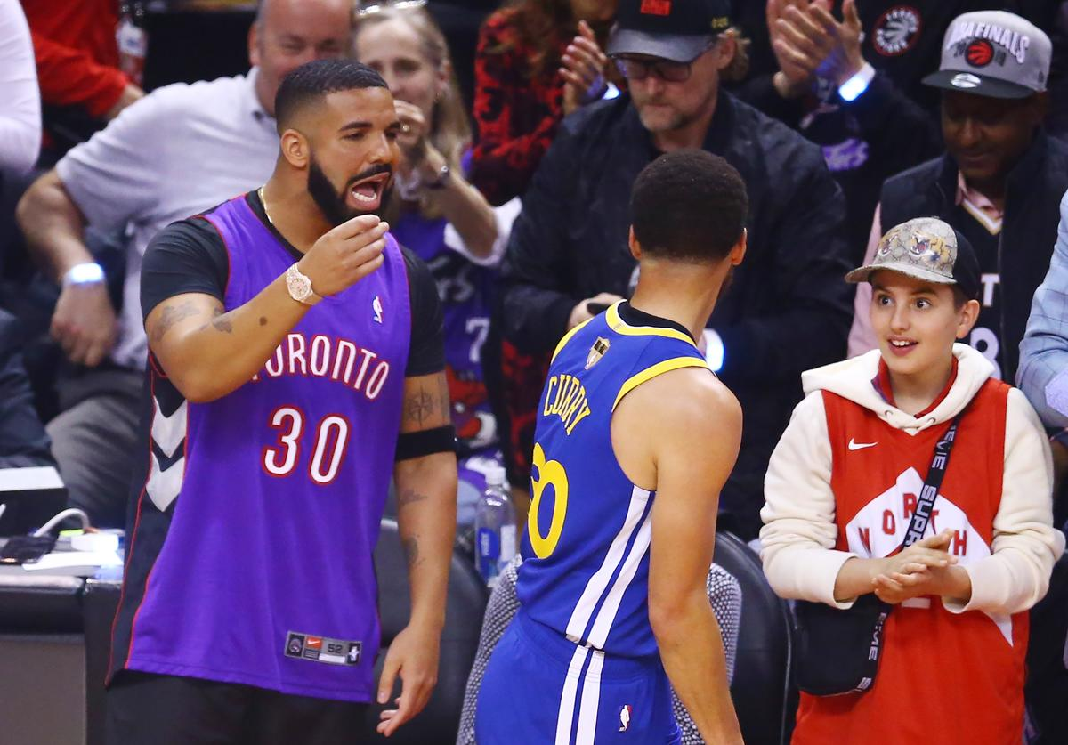 Rapper Drake and Stephen Curry #30 of the Golden State Warriors exchange words during a timeout in the first quarter during Game One of the 2019 NBA Finals between the Golden State Warriors and the Toronto Raptors at Scotiabank Arena on May 30, 2019 in Toronto, Canada.