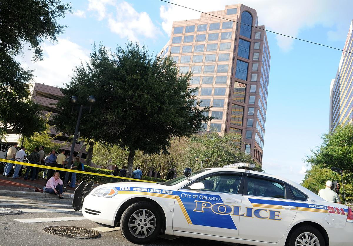 Employees wait outside of the Legions Place office building, where a gunman opened fire wounding several people on November 6, 2009 in Orlando, Florida. The gunman, Jason Rodriguez, 40, who once worked as an engineer in one of the downtown offices, surrendered to the police after firing shots killing so far one and wounding five.