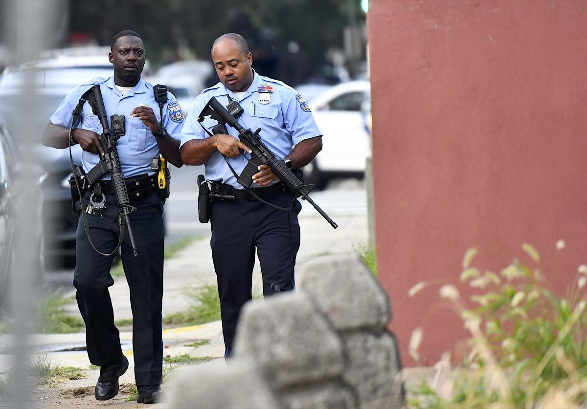 Police officers carrying assault rifles respond to a shooting on August 14, 2019 in Philadelphia, Pennsylvania. At least six police officers were reportedly wounded in an hours-long standoff with a gunman that prompted a massive law enforcement response in the city's Nicetown-Tioga neighborhood.