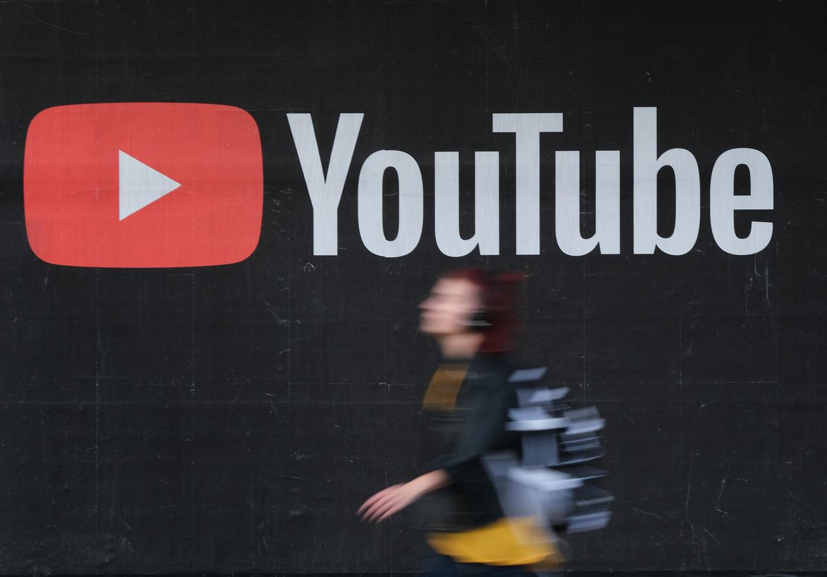 A young woman wearing headphones walks past a billboard advertisement for YouTube on September 27, 2019 in Berlin, Germany.